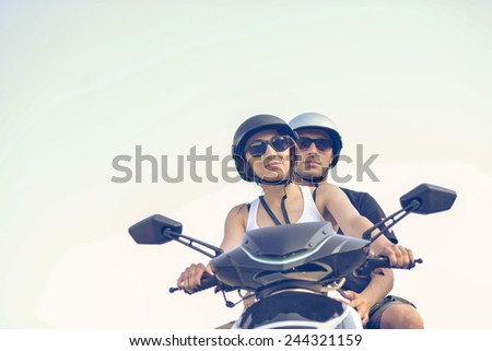 Happy young couple riding scooter  - stock photo