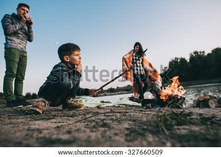 Happy young family sitting around the campfire on the beach at night fall, mother, father, son