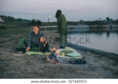 Happy young family sitting around the campfire on the beach at night fall, mother, father, son - stock photo