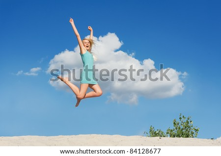 Happy young girl  jumping against blue sky.