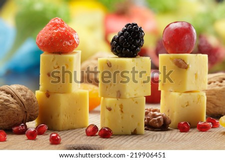 Hard cheese with walnuts   served  on sticks with fruits and berries - stock photo