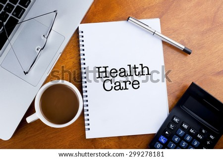 """""""Health Care"""" text on notebook with a cup of coffee, calculator, spectacle and laptop on desk - stock photo"""