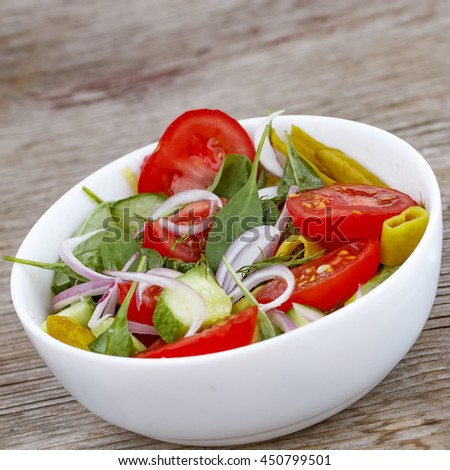 Healthy eating, dieting, vegetarian food and cooking concept - close up of vegetable salad bowl and fork at home. Square shot.