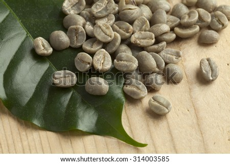 Heap of Pamwamba green unroasted coffee beans and a coffee plant leaf - stock photo