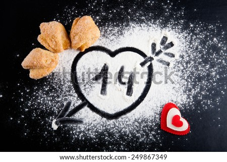 14. Heart with arrow on the flour on the black table. Cookies and red heart.