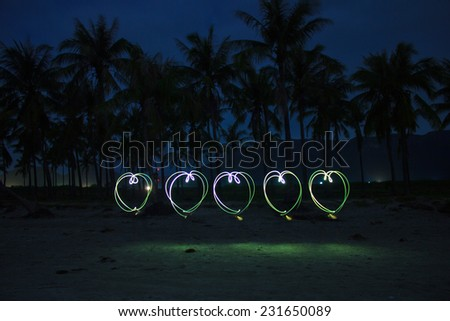 5 hearts painted on the beach with light on long time exposure of camera (bulb mode). This kind of photography is called light brush technique - stock photo