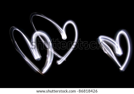 3 hearts painted with light on long time exposure of camera (bulb mode). This kind of photography is called light brush technique - stock photo