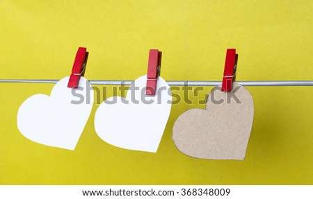 hearts with clothespins hanging on clothesline on yellow background. room for text. Romantic date, love Valentines Day concept - stock photo