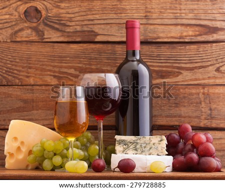 ?heese, grapes and wine bottles on wooden table in restaurant - stock photo