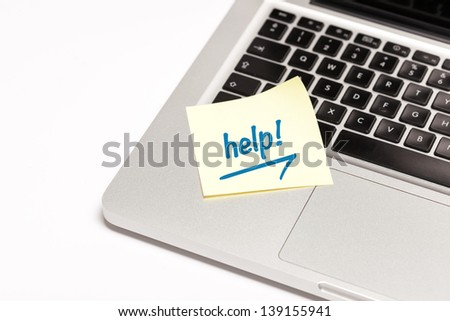 """help"" written on sticky note, on laptop keyboard. - stock photo"