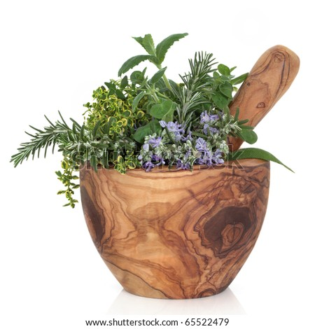 Herb leaf selection of golden thyme, oregano, purple sage, mint and  rosemary in flower in a rustic olive wood mortar with pestle, isolated over white background. - stock photo