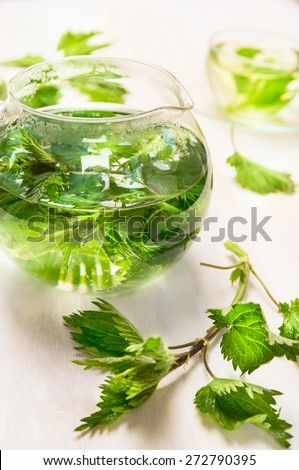 herbal nettle tea in glass pot  on white wooden background, close up