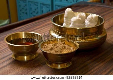 herbs powder and oil in bronze cups, prepared for  traditional indian ayurvedic  massage - stock photo