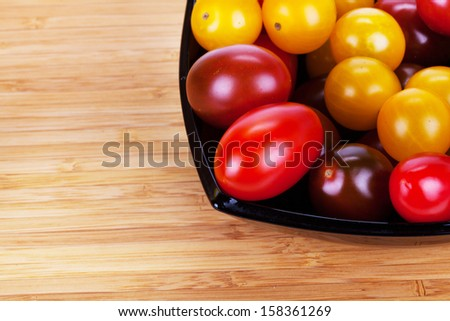 ��¡herry tomatoes in black plate on wooden table - stock photo