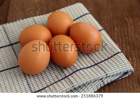 ?hicken brown eggs on a gray napkin on a wooden brown background