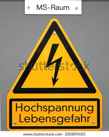 High voltage sign in Germany. The top line means Mittelspannungs-Raum (medium voltage area), the lower lines mean high voltage life danger.  - stock photo