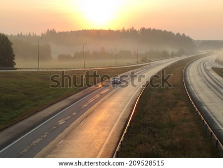 Highway in the early morning at sunrise in the mist - stock photo