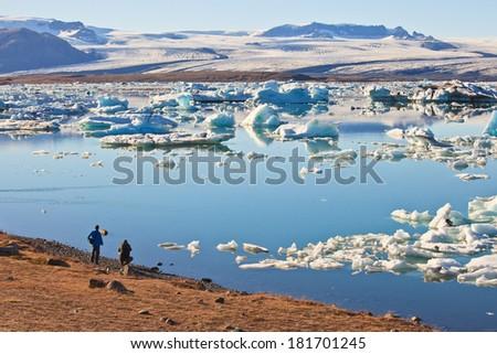 Hikers overlooking Jokulsarlon Lagoon and Vatnajokull Glacier , Iceland  - stock photo