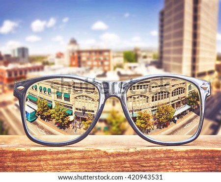 hipster glasses on a park bench or table with a cityscape in the background toned with a retro vintage instagram hdr filter app or action effect  - stock photo