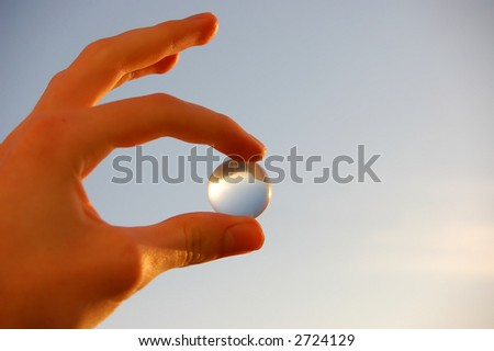 holding glass marble over blue sky - stock photo