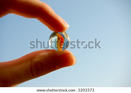 holding glass marble over blue sky macro - stock photo