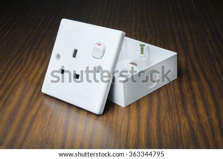 3 hole plug socket in wooden background - stock photo