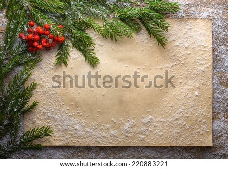 holiday decoration with paper, snow, bells, green branch and rowan on wooden frozen table, christmas background  - stock photo