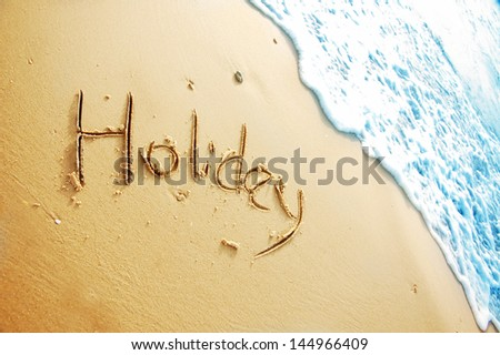 """Holiday"" written in sand beach - stock photo"