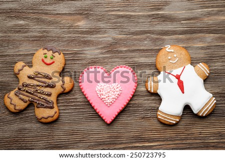 homemade gingerbread couple and cookie in shape of heart for Valentine's Day on wooden table. - stock photo