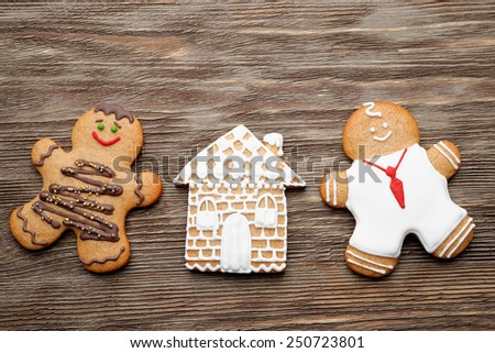 homemade gingerbread couple and home on wooden table - stock photo