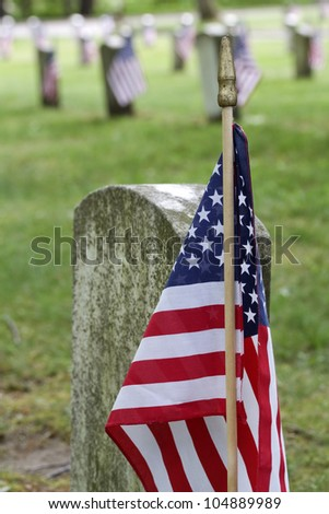 """Honor"" -- A United States flag sits next to the grave of a veteran of the U.S. Armed Forces. - stock photo"