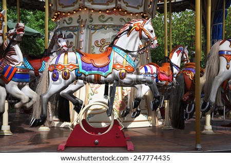 Horses on a carnival Merry Go Round. - stock photo
