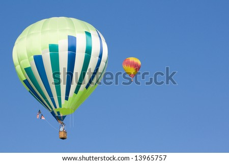 2 hot air balloons hang in the beautiful blue sky - stock photo