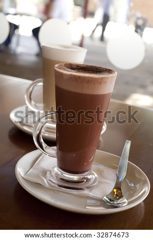Hot chocolate in a tall class with Cafe Latte on background, shallow DOF - stock photo