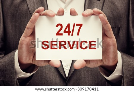 24 hours a day and 7 days a week service written on a card in male hands - stock photo