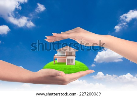 house in human hands representing home ownership and the real estate business against blue sky  - stock photo
