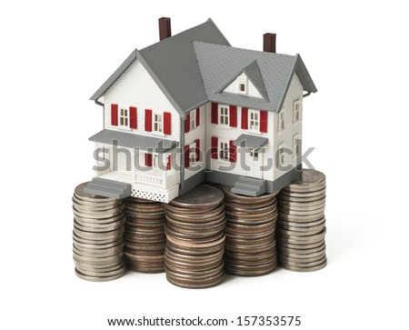 House sitting on stacks of money against white background. Concept of real estate. Clipping path included. - stock photo