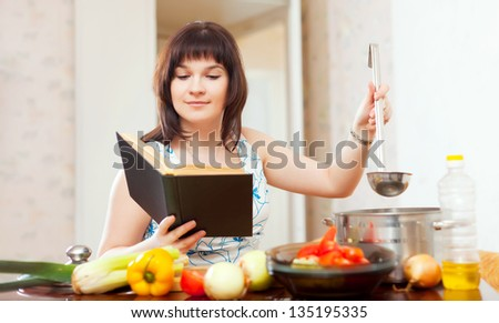 housewife cooking with book and ladle in kitchen