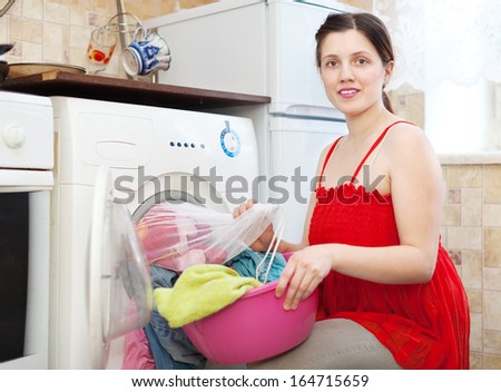 housewife  in red  loading the washing machine with laundry bag