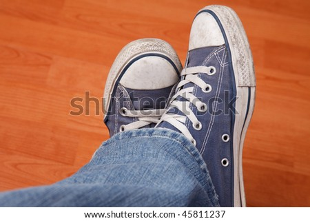 human foot with jeans and sneakers on wooden floor - stock photo