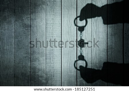 Human Hands Shadow with Handcuffs on Natural Wooden Background. You can see more silhouettes and shadows on my page.  - stock photo