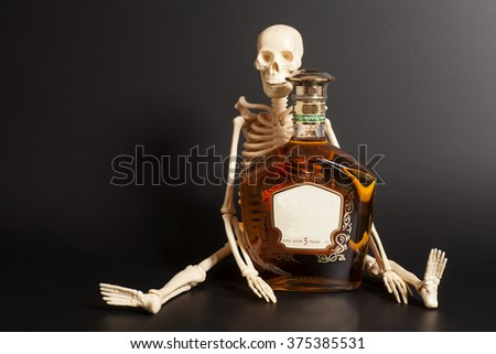 human skeleton with cognac, brandy bottle  on black background - stock photo