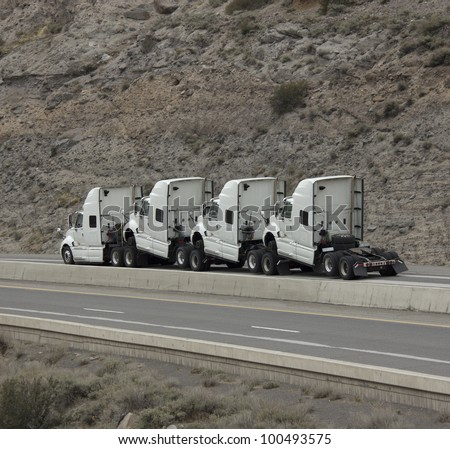 4 humped trucks towing - stock photo