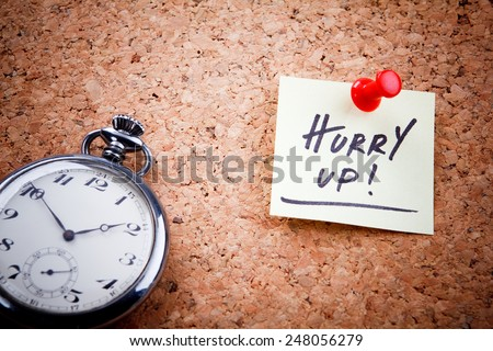"""""""Hurry up!"""" written on a post note and hanged on the cork-board with an old pocket watch. - stock photo"""
