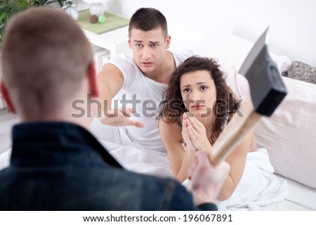 husband with hatchet caught cheating wife  - stock photo