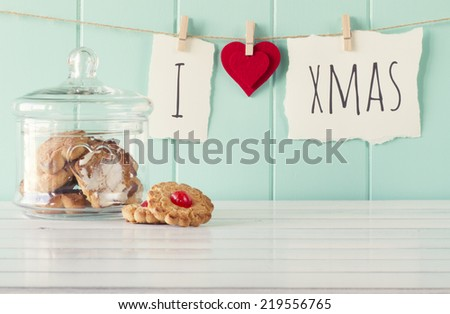 """I love xmas"" hanging on a rope with clothespins. A robin egg blue wainscot as background and a glass jar on a white wooden table. Vintage Style. - stock photo"
