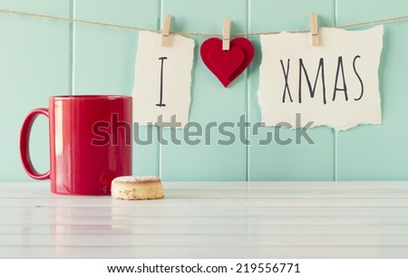"""I love xmas"" hanging on a rope with clothespins. A robin egg blue wainscot as background and a red mug on a white wooden table. Vintage Style. - stock photo"