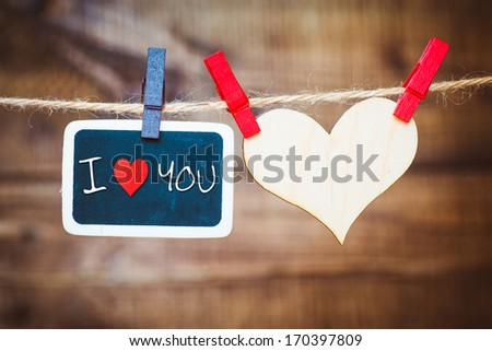 """I Love You"". Instant photo on the clothesline with words ""I Love You"". On old wood background.  - stock photo"