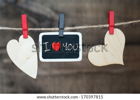 """""""I Love You"""". Instant photo on the clothesline with words """"I Love You"""". On old wood background.  - stock photo"""