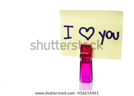 """I love you"" message written on a yellow paper note with a clothespins holding isolated over a white background - stock photo"